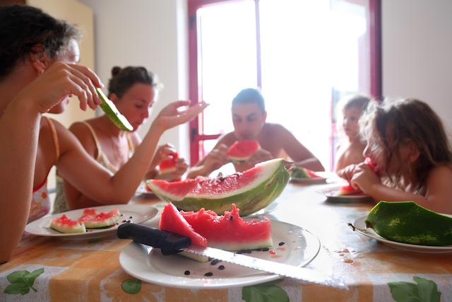 family eats juicy watermelon. Focus on plate with piece of watermelon and knife