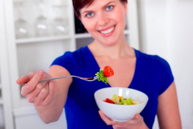 young woman offering a healthy green salad