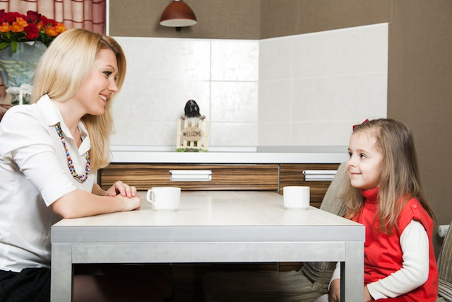 Smiling young mother with daughter at the table