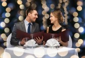 restaurant, couple and holiday concept - smiling couple with menus at restaurant
