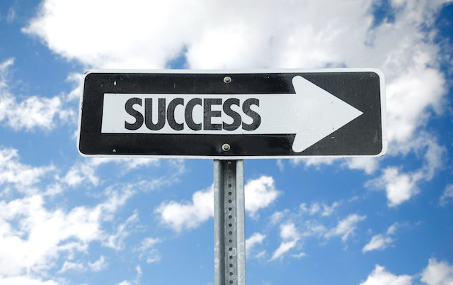 Success direction sign with sky background